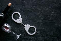 Illegaler Verkauf des Alkoholkonzeptes Handschellen nahe Weinglas und -flasche auf schwarzem Draufsicht-Kopienraum des Hintergrun stockfotos