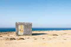 Illegally constructed concrete shelter on limestone cliffs in Go. Zo, Malta close to wied il-mielah. Barren landscape with the sea and blue sky Royalty Free Stock Photography