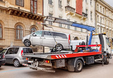 Illegally parked car. Tow truck removes an illegally parked car from the street Stock Image