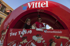 Publicity Caravan- Detail. Illiers-Combray,France- July 21st, 2012: A man and a woman ditribute the official daily newspaper of the Le Tour de France bicycle Stock Image