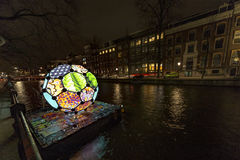 Illimunated and colorful ball on the canal at Amsterdam stock photos