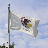Illinois State Flag. The Illinois State Flag flying in the wind against a cloudy blue sky Royalty Free Stock Photos