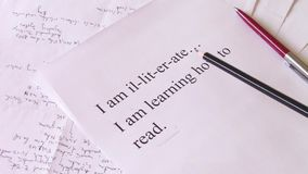 Illiterate person. Following words printed on paper, with pencil in an attempt of learning how to read stock video footage