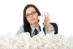 Illnes of working woman. Young businesswoman in office with lot of tissues around - flue concept Royalty Free Stock Image