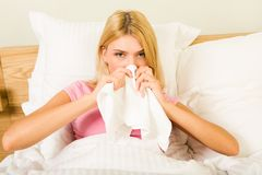 During illness. Photo of sick woman sitting in bed with tissue and blowing her nose into it Royalty Free Stock Photography