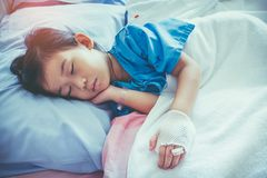 Illness asian child admitted in hospital with saline intravenous. Closeup of illness asian child admitted in hospital with saline intravenous IV on hand. Girl Royalty Free Stock Photo