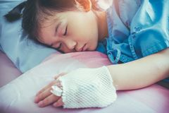 Illness asian child admitted in hospital with saline intravenous. Closeup of illness asian child admitted in hospital with saline intravenous IV on hand. Girl Stock Photos