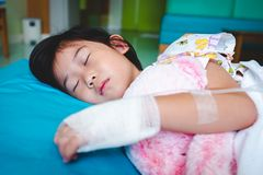 Illness asian child admitted in hospital with saline intravenous on hand. Closeup of illness asian child admitted in hospital with saline intravenous IV on hand royalty free stock images