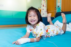 Illness asian child admitted in hospital with saline intravenous on hand. Illness asian child smiling happily and looking at camera. Girl admitted in hospital stock images