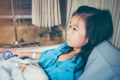 Illness asian child admitted in hospital with saline intravenous. IV on hand. Girl inattentive and feeling sad. Kid emotion, facial expression. Human health Royalty Free Stock Photos