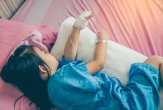 Illness asian child admitted in hospital with saline intravenous. IV on hand. Cute girl sleeping at comfortable equipped hospital room with sunlight. Health royalty free stock photos