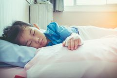 Illness asian child admitted in hospital with saline intravenous. IV on hand. Girl sleeping at comfortable equipped hospital room with sunlight. Health care Royalty Free Stock Photo