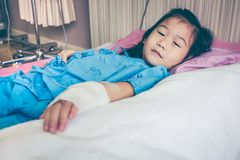 Illness asian child admitted in hospital with saline intravenous. Illness asian child lying down on sickbed and looking at camera, admitted in hospital and Stock Image