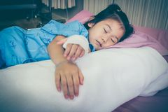 Illness asian child admitted in hospital with saline intravenous. IV on hand. Cute girl sleeping at comfortable equipped hospital room. Health care stories royalty free stock photo
