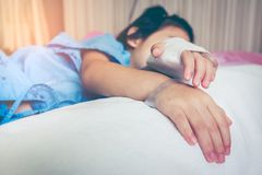 Illness asian child admitted in hospital with saline intravenous. IV on hand. Cute girl sleeping at comfortable equipped hospital room. Focus on hand. Health royalty free stock images