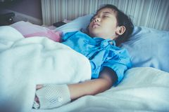 Illness asian child admitted in hospital with saline intravenous. IV on hand. Girl sleeping at comfortable equipped hospital room with sunlight. Health care royalty free stock image