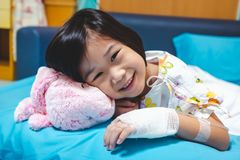 Illness asian child admitted in hospital with saline iv drip on hand.  Health care stories. Close up. Illness asian child smiling happily and looking at camera stock photo