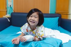 Illness asian child admitted in hospital with saline iv drip on hand.  Health care stories. Illness asian child smiling happily and looking at camera. Girl stock photos