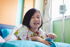 Illness asian child admitted in hospital with saline iv drip on hand.  Health care stories. Illness asian child smiling happily and looking at camera. Girl stock image