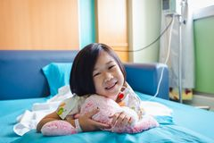 Illness asian child admitted in hospital with saline iv drip on hand.  Health care stories. Illness asian child smiling happily and looking at camera. Girl royalty free stock photography