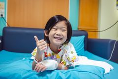 Illness asian child admitted in hospital with saline iv drip on hand.  Health care stories. Illness asian child smiling happily and showing thumb up hand sign royalty free stock photography