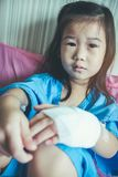 Illness asian child admitted in hospital with saline iv drip on. Illness asian child admitted in hospital while saline intravenous IV on hand. Unhappy girl Stock Photos