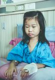 Illness asian child admitted in hospital with saline iv drip on. Illness asian child admitted in hospital while saline intravenous IV on hand. Unhappy girl Royalty Free Stock Photography