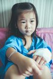 Illness asian child admitted in hospital with saline iv drip on. Illness asian child admitted in hospital while saline intravenous IV on hand. Unhappy girl Stock Photography