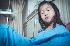 Illness asian child admitted in hospital with saline iv drip on Royalty Free Stock Image