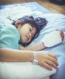 Illness asian child admitted in hospital with saline iv drip on. Unhappy illness asian child lying on side while saline intravenous IV drip on hand, admitted in stock images