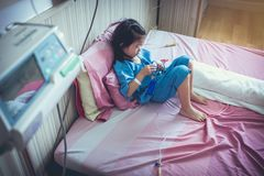 Illness asian child admitted with saline iv drip on hand. Stock Images