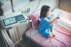 Illness asian child admitted with saline iv drip on hand. Illness asian girl admitted in hospital with infusion pump feeding IV drip. Shallow depth of field DOF Stock Photo