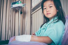 Illness asian child admitted in hospital with saline intravenous. Illness asian child looking at camera, admitted in hospital with infusion pump and saline Royalty Free Stock Photo