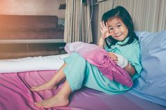 Illness asian child admitted in hospital with saline intravenous. Illness asian child looking at camera with bright sunlight. Playful girl admitted in hospital royalty free stock photo