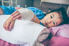 Illness asian child admitted in hospital with saline intravenous. Illness asian child lying down on sickbed and looking at camera, admitted in hospital and royalty free stock images