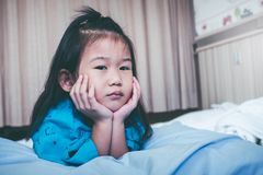 Unhappy illness asian child admitted in hospital. Vintage tone. Illness asian child on sickbed and looking at camera, admitted in hospital. Unhappy girl feeling Stock Photos