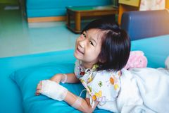 Illness asian child admitted in hospital with saline iv drip on hand.  Health care stories. Illness asian child smiling happily and looking at camera. Girl royalty free stock image
