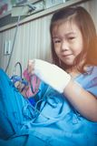 Illness asian child admitted in hospital with IV drip on hand. Royalty Free Stock Photos