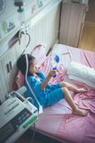 Illness asian child admitted with saline iv drip on hand. Illness asian girl admitted in hospital with infusion pump feeding IV drip. Shallow depth of field DOF Stock Images