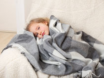 Illness child. Little girl wrapped in a blanket stock photos