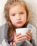Illness child. Little girl wrapped in a blanket with mug royalty free stock images