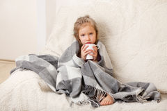 Illness child. Little girl wrapped in a blanket with mug stock photo