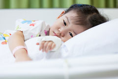 Illness child in hospital, saline intravenous (IV) on hand asian Stock Photo