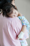 Illness child in hospital, saline intravenous (IV) on hand asian. Mother carrying her daughter,  illness child in hospital, saline intravenous (IV) on hand asian Royalty Free Stock Photos