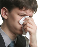Illness come. Ill young man with sad eyes and kleenex on his nose Royalty Free Stock Photos