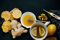 Illness concept: Tea with lemon, thermometer, ginger, scarf, tab Stock Image