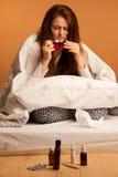Illness flu - ill woman drink tea in bed Stock Photos