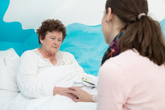 Illness: Older woman lying sick in the bed. Royalty Free Stock Photos