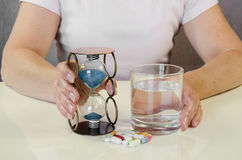 Illness and time. Person holding pill, sandglass and glass of water Stock Photos