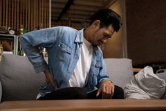 Asian man sitting on sofa having backache and holding his back at home. stock images